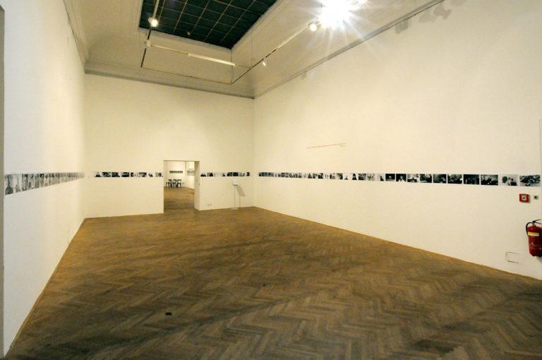 Ausstellungsansicht. ein schmaler Streifen schwarzweiss fotos auf allen drei seiten eines großen Raumes