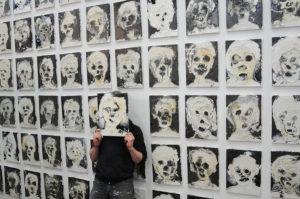 Mann vor einer Wand mit vielen Selbstporträts- er hält sich ein Selbstporträt vor das Gesicht