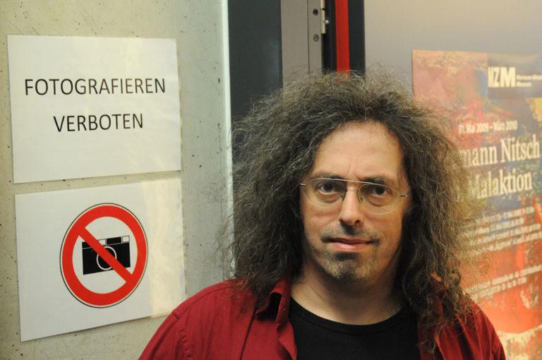 """Porträt eines langhaarigen Mannes vor einer Wand mit dem SChild """"Fotografieren verboten"""""""