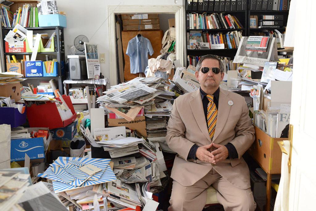 Mann mit Sonnenbrille, Anzug und gefaltenen Händen in seiner Wohnung, die voll und messiartig Unordnung ausströmt