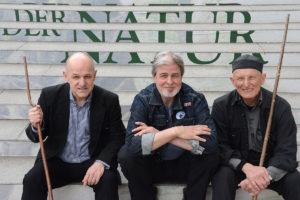 Drei Männer sitzen auf den Stufen vor der Albertina