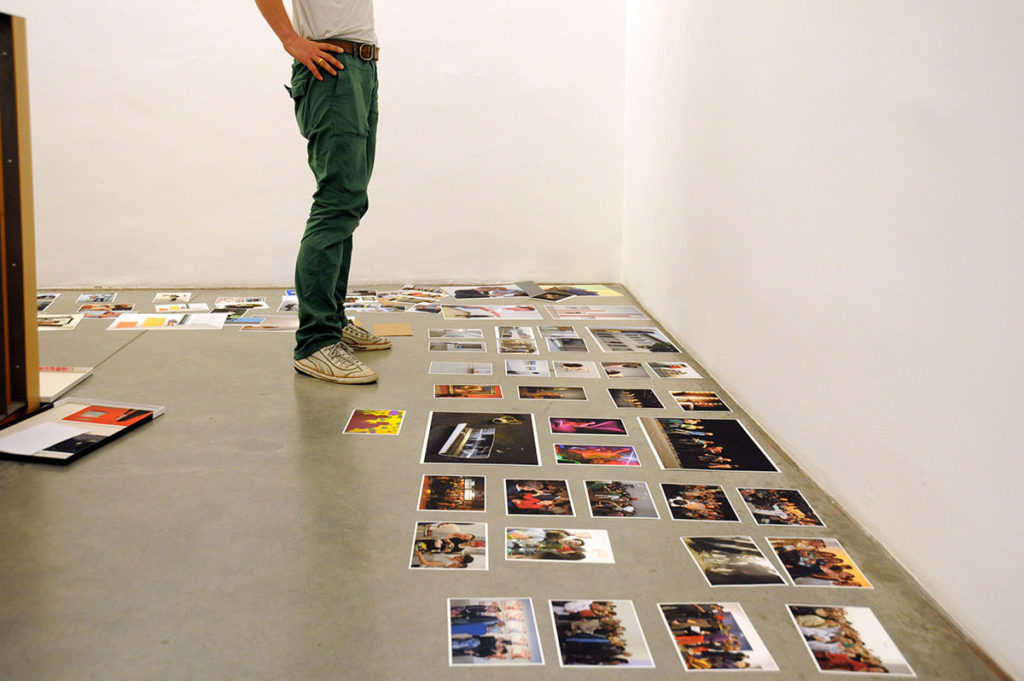 Boden bedeckt mit Fotos. Ein Mann(nur seine Beine sichtbar) steht davor