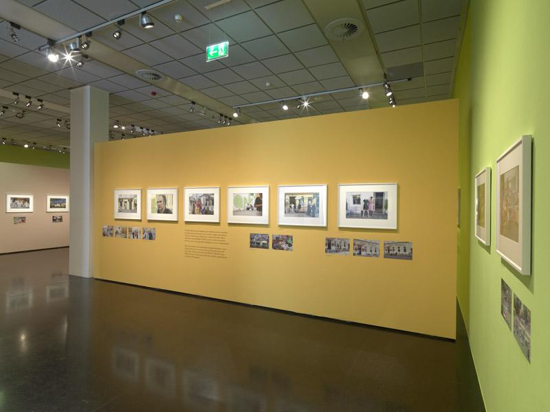 Einblick in eine Ausstellung mit großen Schwarz Weiss Fotos auf orange gefärbelter Mauer